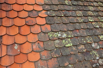 A red tile roof with algae and mold growth.