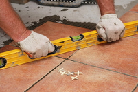 Leveler being used to check the angle of laid outdoor tile