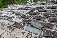 A roof with shingles coming off.