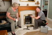 A certified technician speaking to an older homeowner about her fireplace.