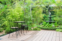 A garden fountain sits beside a backyard deck, surrounded by foliage.