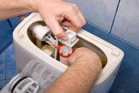 A man fixes the toilet tank