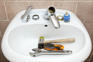A sink full of plumbing tools.