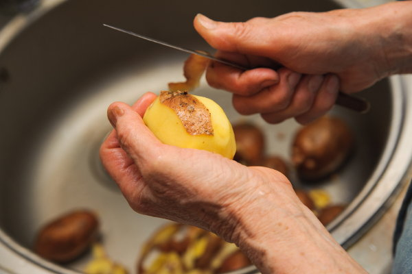 A pair of elderly hands peeling potatoes with a knife over the sink.