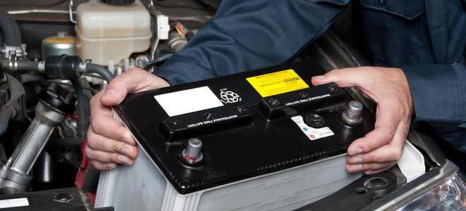 Um mecânico de carro colocando uma bateria nova no motor.