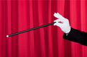magician's hand performing a trick while holding a wand