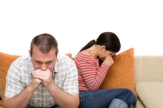 couple sitting on couch with woman crying