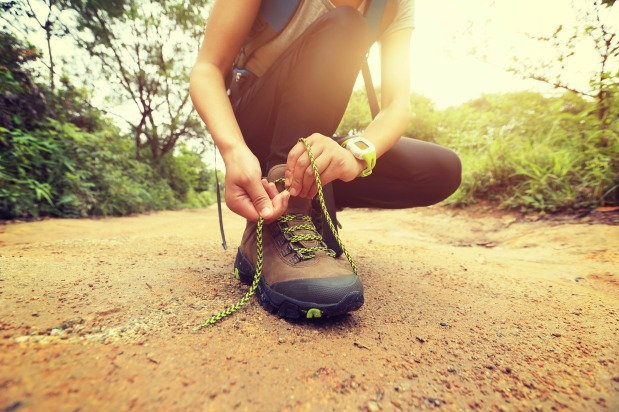 Person ties shoe before embarking on a journey