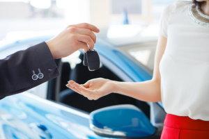 Man handing women car keys.