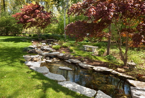 A backyard pond edges with natural stone slabs.