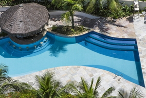 beautiful pool area with stone deck, gazebo, and palm trees from above