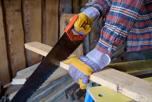 A person using a saw on a piece of lumber.