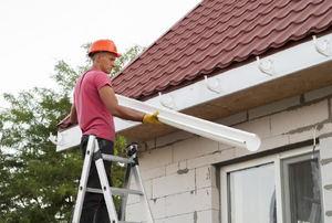 A man installs gutters.