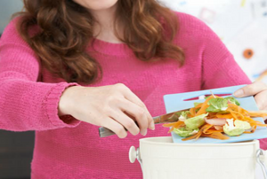 A woman dumping food scraps into a small bucket.