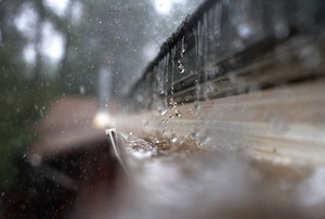 A close-up of rain falling into a gutter on a house.