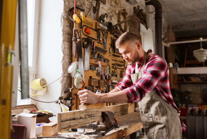 Man using a wood planer in a shop
