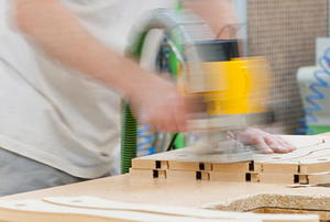 A woodworker using a router to cut MDF.