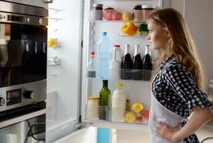 A woman standing in front of an open refrigerator.