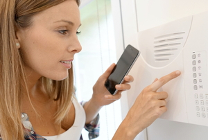A woman programs her security system.