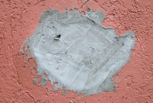 a hole in a pink stucco wall