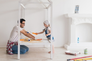 man and girl painting a child's bed