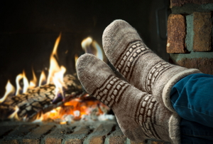 A pair of woolen socks in front of a fire in a fireplace.