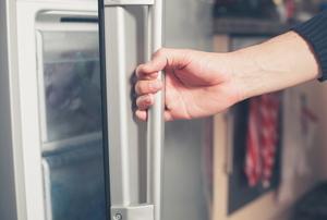 Opening the door of an upright freezer