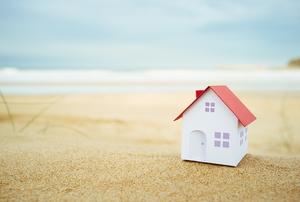 A tiny white cardboard house sitting on the beach.