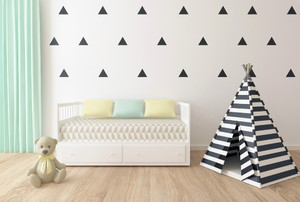 A kid's room with triangles stenciled on the wall.