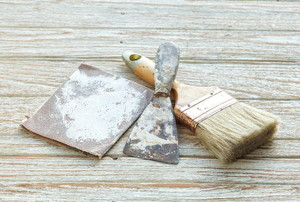 sandpaper, a scraper, and a paintbrush on wood