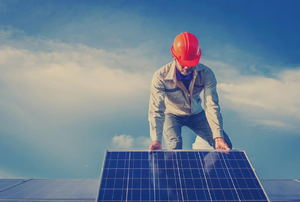A construction worker on a roof with a solar panel.