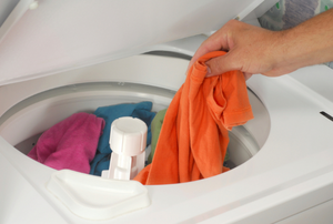 Person adding clothing to a washing machine