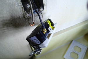 outlet dangling from the wall