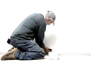 A senior man painting a wall with white paint.
