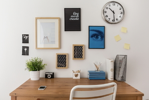 A gallery wall of art above a desk.