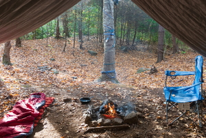diy tent in campsite with fire, chair, and sleeping bag