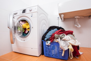 A washing machine next to a laundry basket.