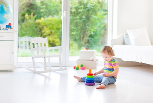A toddler playing with toys on her bedroom floor.