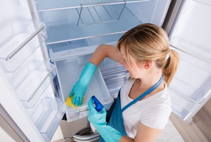 A woman cleaning a refrigerator