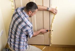 A man trimming spray foam around a door frame.