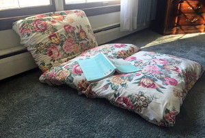 A child's bed made from pillows.