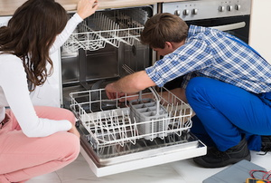 man and woman working on a dishwasher
