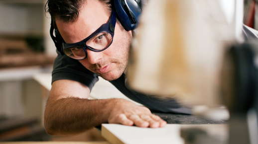 Image of a man wearing goggles while cutting wood.