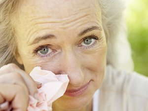 Image of an elderly woman holding a tissue.