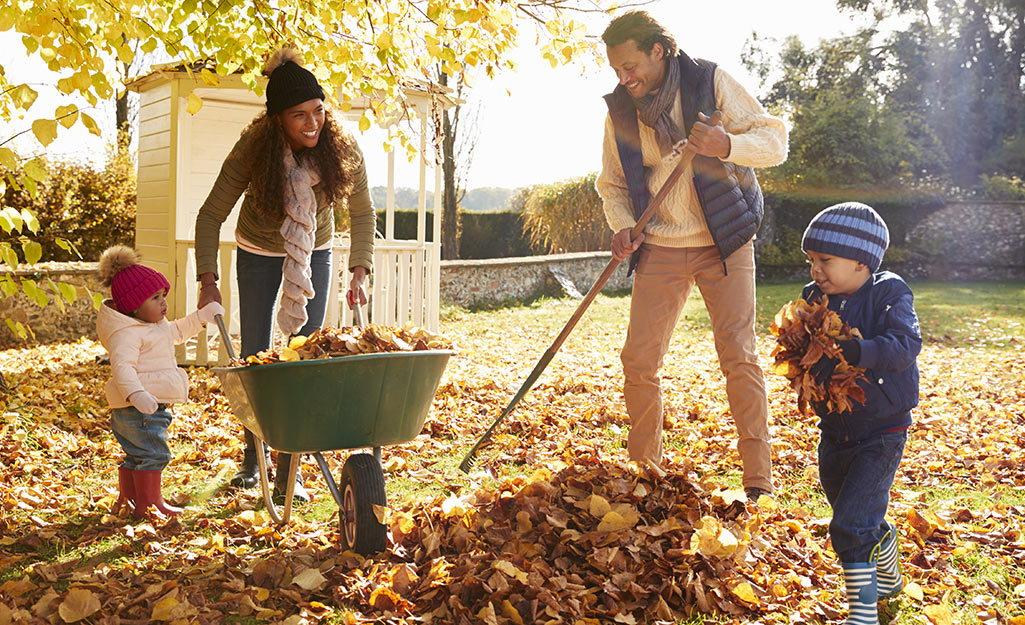 family raking leaves