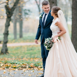 Bride and groom outdoors with fall foliage.