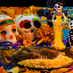 Mexican Day of the Dead table with food and sugar skull figurines