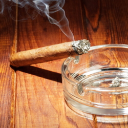 Smoking cigarette against a glass ashtray
