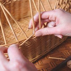 Hands weaving a basket