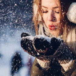 girl blowing snowflakes from hands